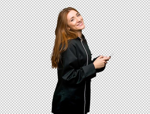 携帯電話でメッセージを送信する若い赤毛のシェフの女性