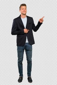 横に指を指している金髪のハンサムな男