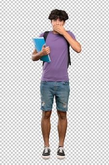 手で口を覆っている若い学生男