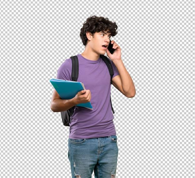 Молодой студент мужчина ведет разговор с мобильным телефоном