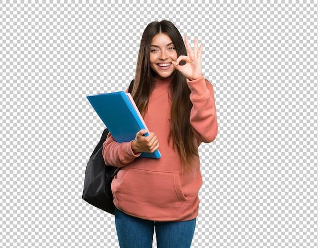 Молодая женщина студента держа тетради показывая одобренный знак с пальцами
