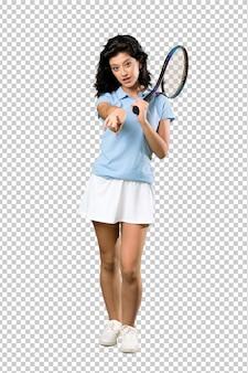 若いテニスプレーヤーの女性が驚いて、フロントを指す