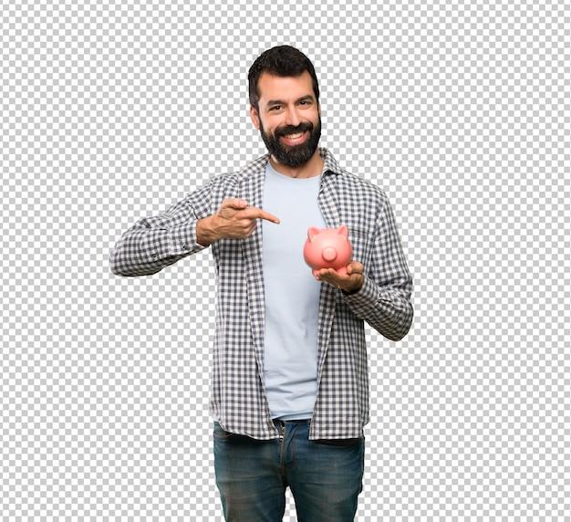 Красивый мужчина с бородой держит копилку