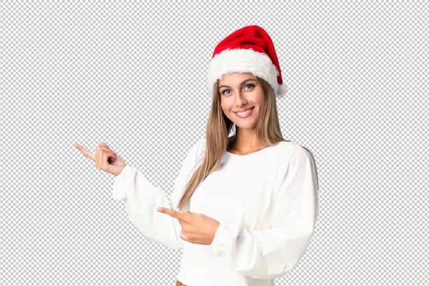 Блондинка в новогодней шапке указывает пальцем в сторону
