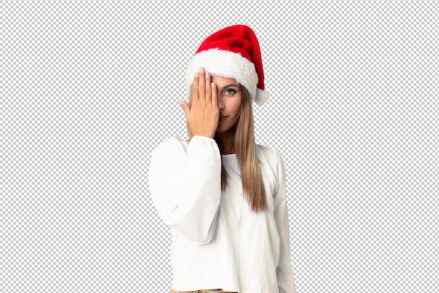 手で目を覆っているクリスマス帽子とブロンドの女の子