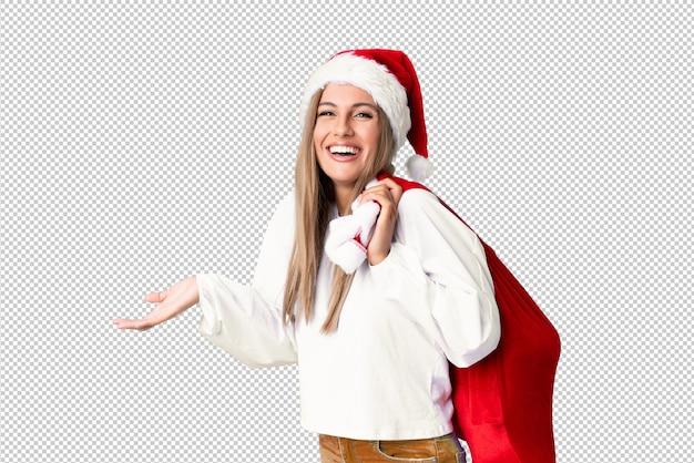 プレゼントの完全な袋を拾って若いブロンドの女性