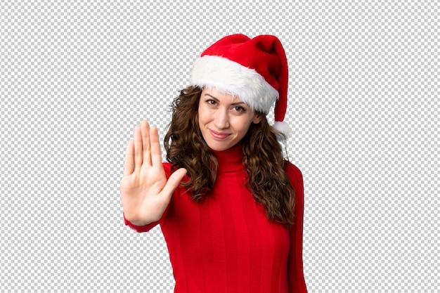 彼女の手で停止ジェスチャーを作るクリスマス帽子の少女