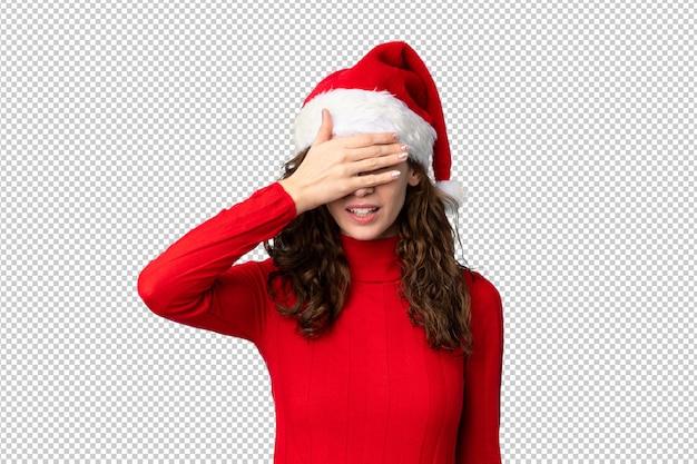 Девушка с шляпой рождества покрывая глаза руками