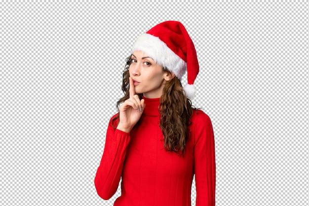 沈黙のジェスチャーをしているクリスマス帽子の少女