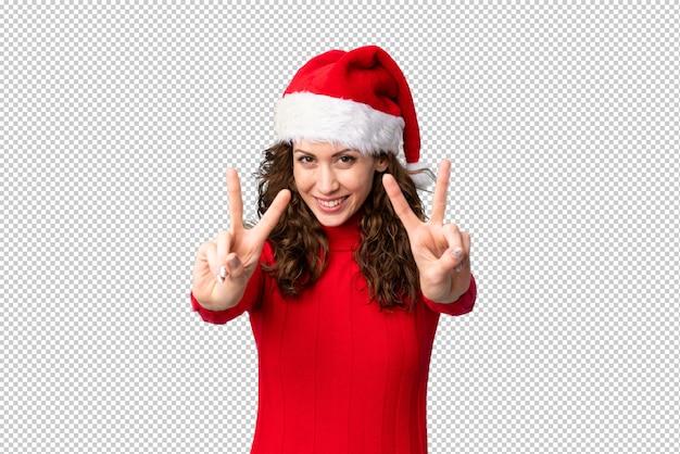 笑顔と勝利のサインを示すクリスマス帽子の少女