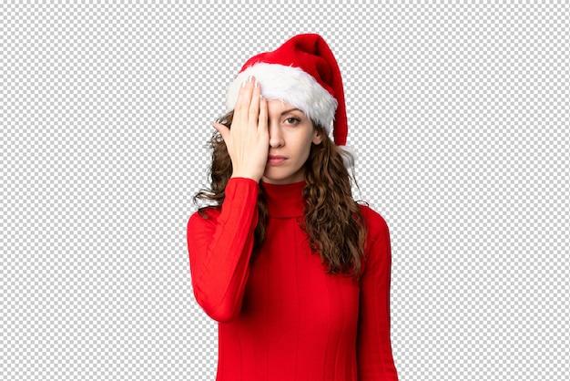 手で目を覆っているクリスマス帽子の少女