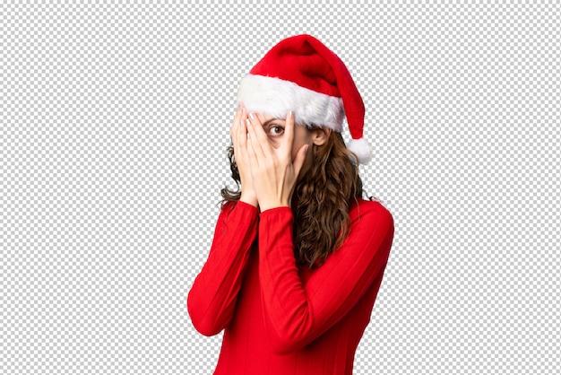 目を覆っていると指を通して見るクリスマス帽子の少女