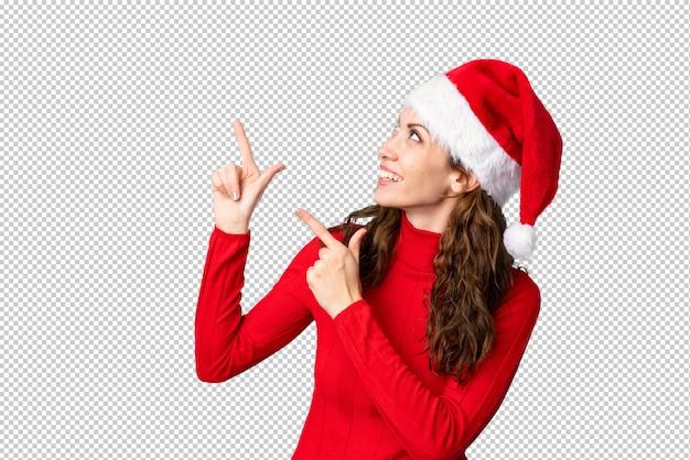 人差し指で素晴らしいアイデアを指しているクリスマス帽子の少女
