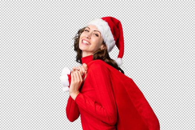 ギフトのクリスマスバッグを保持しているクリスマス帽子の少女