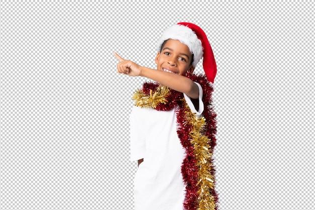 製品を提示する側を指しているクリスマス帽子のアフリカ系アメリカ人の少年