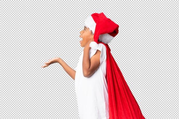 アフリカ系アメリカ人の少年のクリスマス帽子と贈り物の袋を取ると驚きのジェスチャーを行う