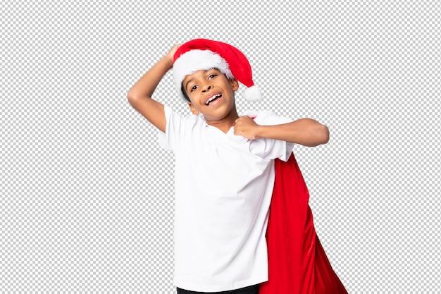 クリスマス帽子と贈り物の袋を取るアフリカ系アメリカ人の少年