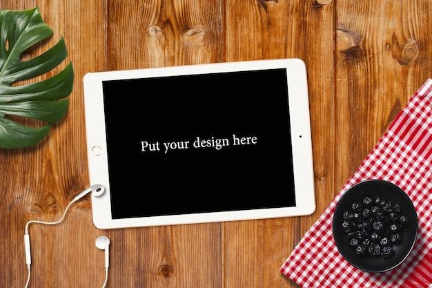 木製のテーブルにモックアップのタブレット画面