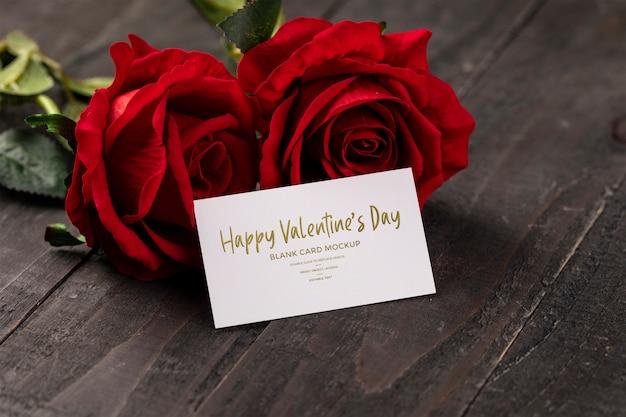 赤いバラのモックアップと空のグリーティングカード