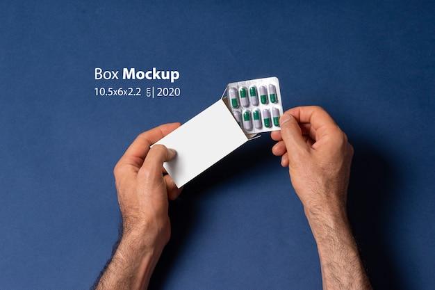 ボックスにカプセル錠剤タブレットを入れて男性の手