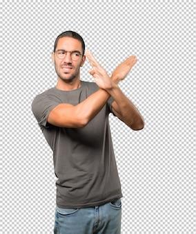 若い男が腕と交差しないのジェスチャーを作る