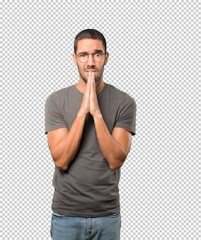 かかわっている若い男性のジェスチャーを祈る