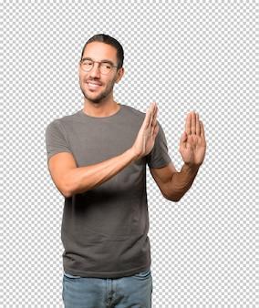 彼の手のひらで停止のジェスチャーを作る幸せな若い男