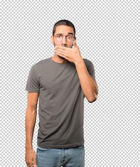 Молодой человек закрыл рот руками