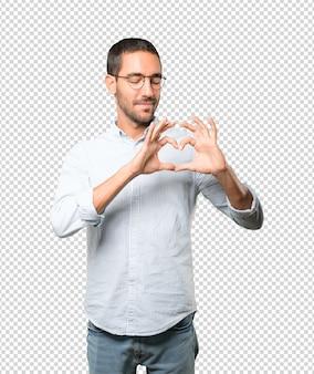 彼の手で愛のジェスチャーをしている幸せな若い男