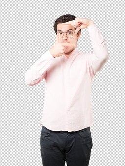 手で写真を撮るジェスチャーを作る驚いた若い男