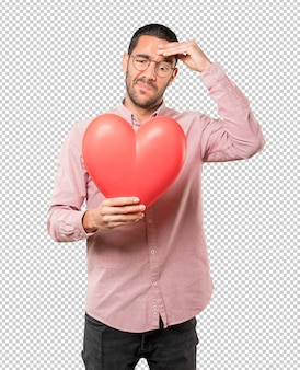 Счастливый молодой человек держит большое игрушечное сердце и делает жесты о дне святого валентина
