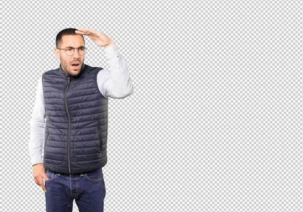 Концентрированный молодой человек с жестом глядя в сторону