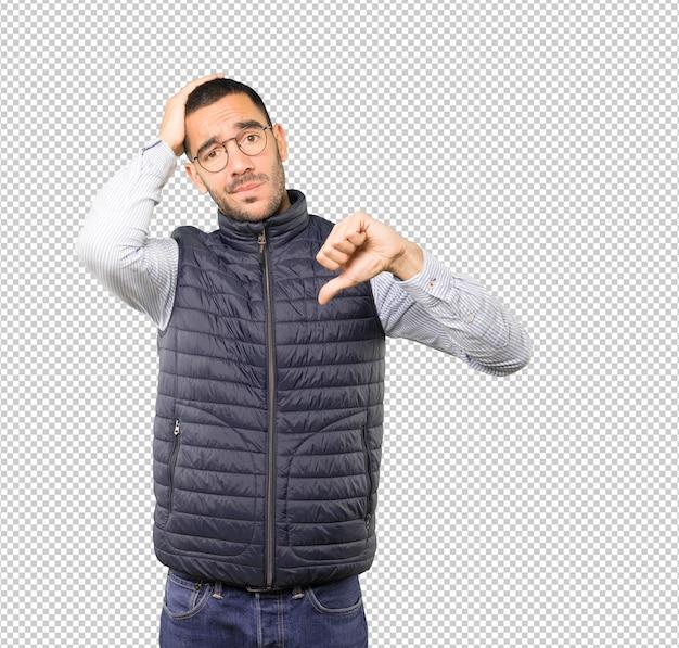 Серьезный молодой человек делает жест побежденного