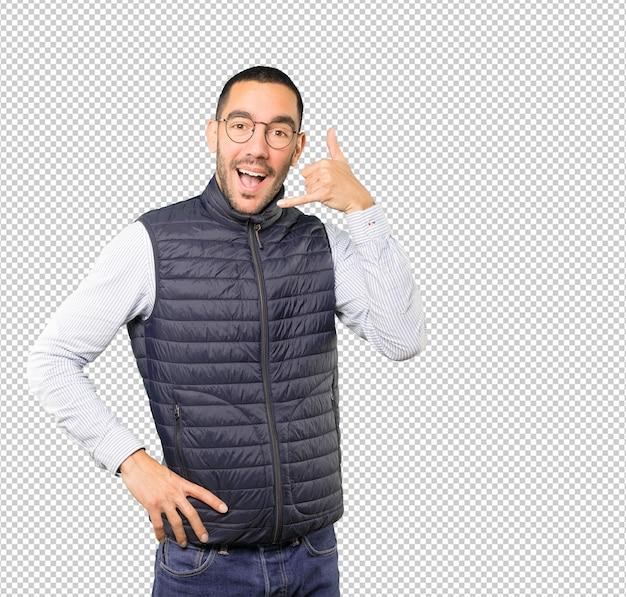 Удивленный молодой человек делает жест звонка рукой