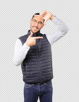 手で写真を撮るジェスチャーを作るフレンドリーな若い男