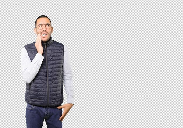 Обеспокоенный молодой человек с жестом зубной боли