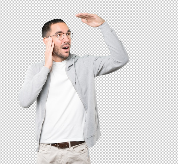 Удивленный молодой человек с жестом глядя в сторону