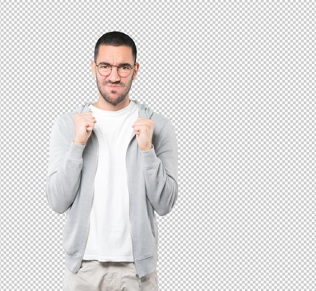 Сердитый молодой человек позирует на прозрачной поверхности