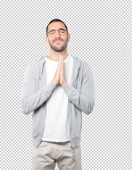 ジェスチャーを祈って幸せな若い男