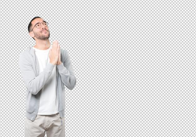 Счастливый молодой человек молится жестом