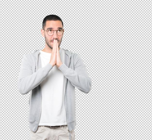 かかわっている若い男のジェスチャーを祈る