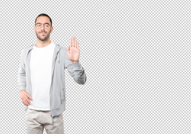 Серьезный молодой человек делает жест остановки ладонью