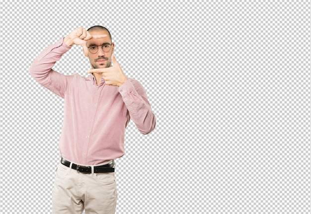 手で写真を撮るジェスチャーを作る驚かれる若い男
