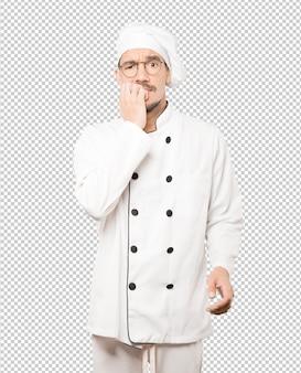 Сумасшедший молодой повар делает нервный жест
