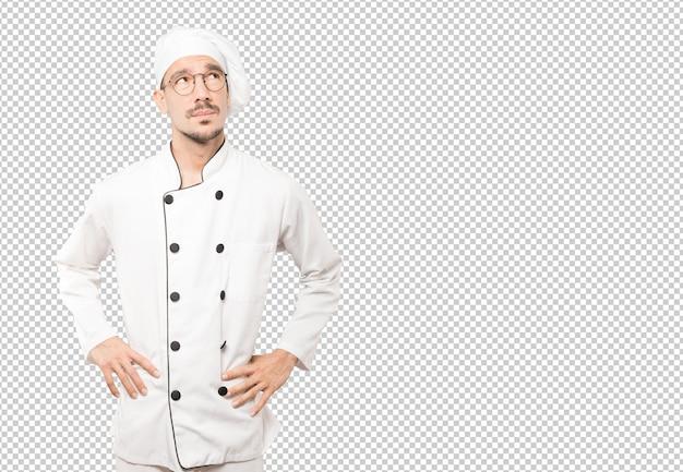 Серьезный молодой шеф-повар, глядя на фоне