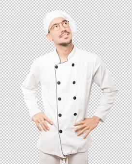Счастливый молодой шеф-повар, глядя на фоне