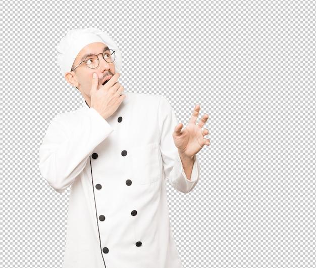 Испуганный молодой шеф-повар кричать на фоне