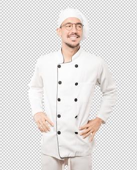 Счастливый молодой шеф-повар позирует на фоне