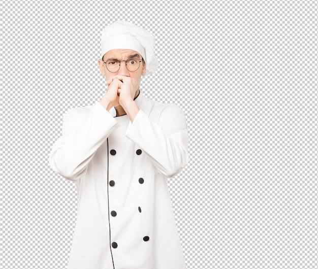 Сердитый молодой шеф-повар позирует на фоне