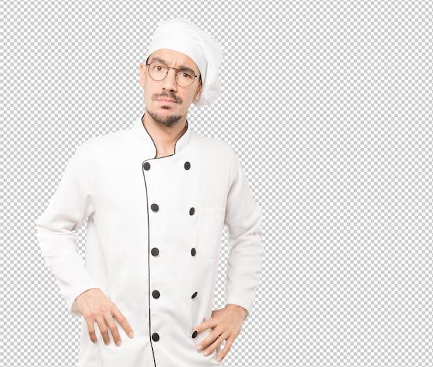 Обеспокоенный молодой повар делает жест сомнения